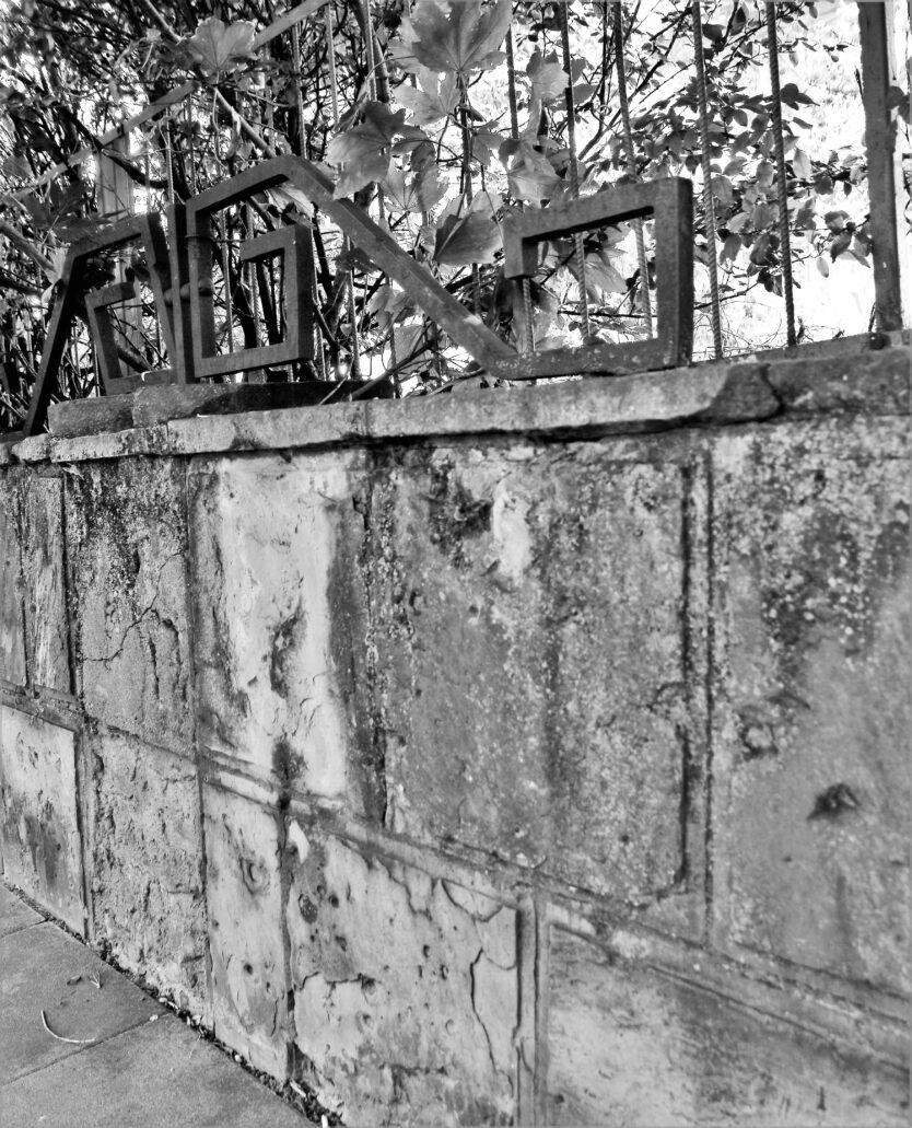 Obłożony kamieniem murek oporowy od strony ulicy Bartoszewicza. Jeszcze kilkanaście lat temu pomiędzy murkiem a kamienicą działała stacja benzynowa. Na murku widać ślady po odłamkach lub uderzeniach pocisków z czasów II wojny światowej. Szczególną uwagę zwraca stylizowane, metalowe ogrodzenie – obok ogrodzenia wzdłuż Alei Przyjaciół najciekawsze tego rodzaju rozwiązanie z lat 30. w Warszawie, godne ochrony konserwatorskiej, tym bardziej, że także na nim widnieją ślady po przestrzelinach z czasów drugiej wojny światowej. Fot. Jerzy S. Majewski