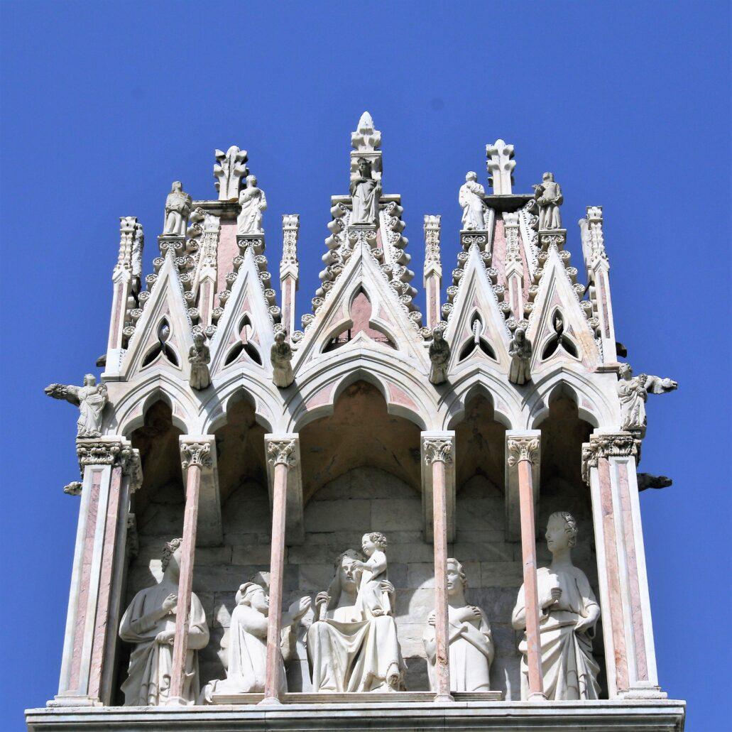 Piza. Campo Santo. Gotycki baldachim z koronkową dekoracją wimpergową i rzeźbą tronującej Matki Boskiej z Dzieciątkiem (towarzyszą jej święci i donatorzy). Włoscy badacze przypisują kompozycję Lupo di Francesco, architektowi i rzeźbiarzowi, uczniowi Giovanniego Pisano i autorowi m.in. kościoła St. Maria del Spina w Pizie, o koronkowej, gotyckiej architekturze zewnętrznej oraz grobu św. Eulalii w katedrze w Barcelonie. Fot. Jerzy S. Majewski