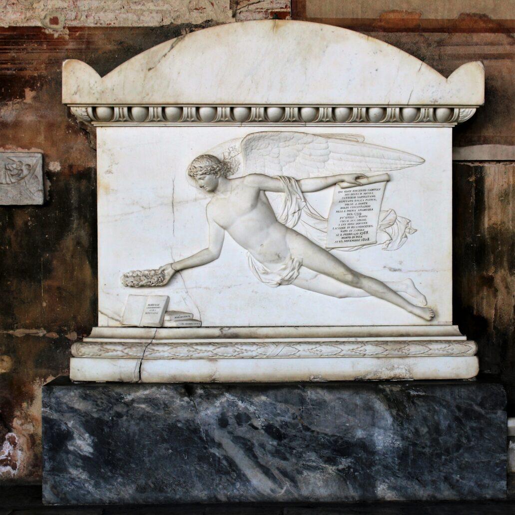 Piza. Campo Santo. Jeszcze jeden Geniusz z wieńcem laurowym na klasycystycznym, marmurowym nagrobku Vincezo Marulliego, zmarłego w 1808 r. Marulli pochodził z neapolitańskiego rodu książęcego. Był intelektualistą epoki Oświecenia. Jako przeciwnik konserwatywnych rządów Burbonów, stał się wielkim zwolennikiem Republiki Neapolitańskiej założonej w 1799 r. przez Napoleona. Był też twórcą wizyjnych projektów zmodernizowania Neapolu. Fot. Jerzy S. Majewski