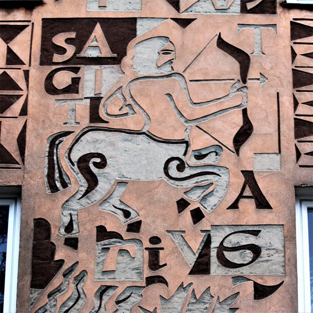 Białystok. Budynek przy Lipowej 1. Większa część elewacji budynku od strony Lipowej ozdobiona została dwuwarstwowymi, znakomitymi sgraffitami autorstwa Krzysztofa Tura z wyobrażeniami znaków zodiaku. Na zdjęciu Strzelec z wkomponowanym napisem łacińskim Sagittarius. Fot. Jerzy S. Majewski