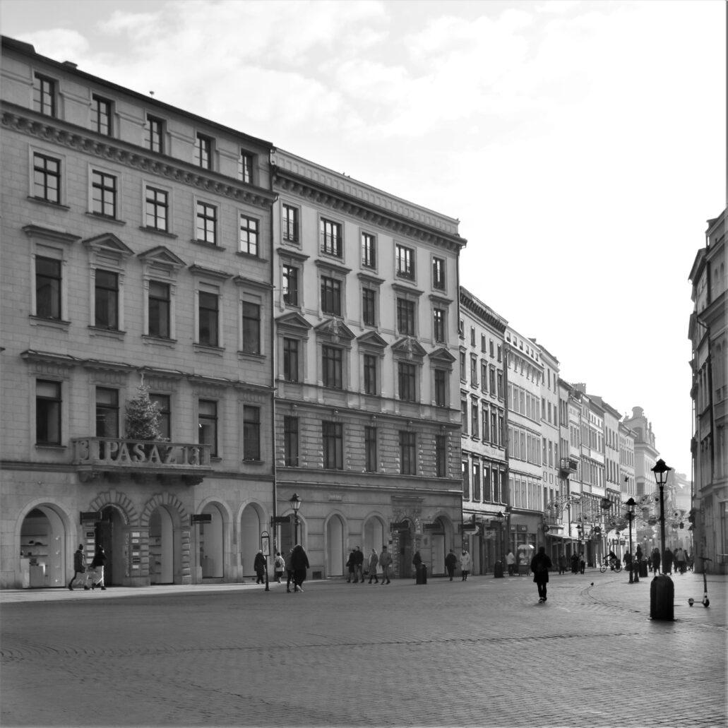 Kraków. Kamienice w lejkowatym ujściu Grodzkiej do Rynku Wielkiego. W szeregu kamienic po lewej stronie znajduje się luksusowy dom handlowy Vitkac (adres Rynek Główny 13) o wnętrzach pełnych wyeksponowanych detali architektonicznych. Ponieważ nie jest galerią handlową, to luksusowe sklepy w nim są otwarte, sprawiając obecnie wrażenie oazy pełnej życia i światła. Fot. Jerzy S. Majewski
