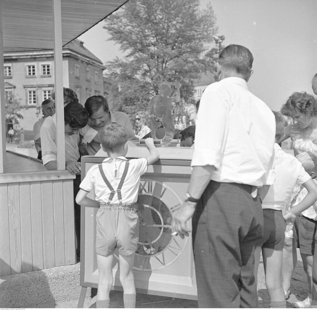 Warszawa. Plac Zamkowy. Zamek odbudowywany był m.in. z ofiar społecznych. Na Placu Zamkowym stanęła przeźroczysta skarbonka, do której wrzucane były pieniądze. Można je był oglądać przez szyby. Opróżnianie skarbonki za każdym razem relacjonowane było przez prasę. Zdjęcia z lata 1972 r. Fot. Grażyna Rutowska. Narodowe Archiwum Cyfrowe