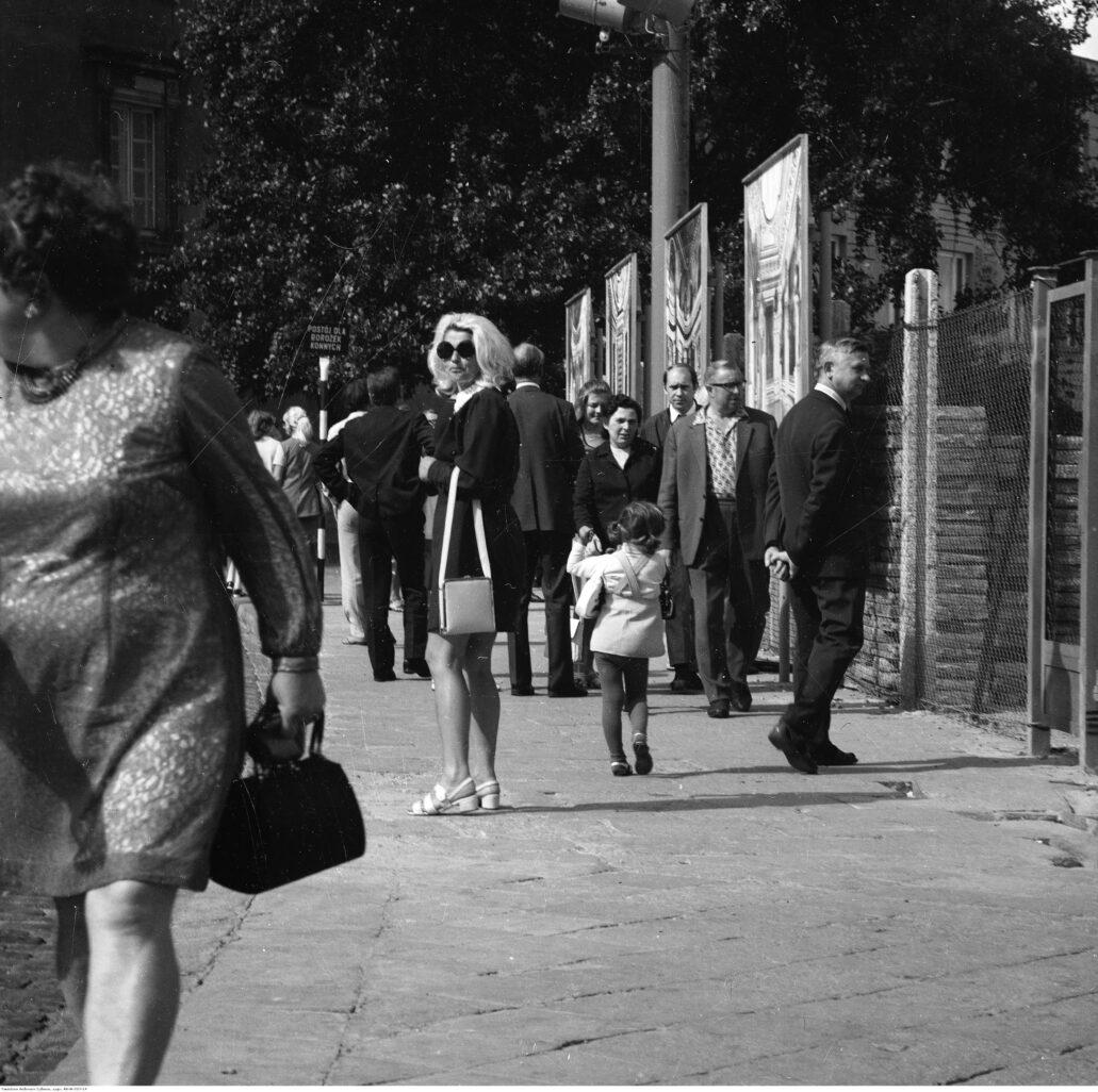 Warszawa. Plac Zamkowy. Wzdłuż ogrodzenia terenu zamkowego zamontowane zostały tablice z widokami wnętrz zamkowych sprzed 1939 r. Fot. Narodowe Archiwum Cyfrowe