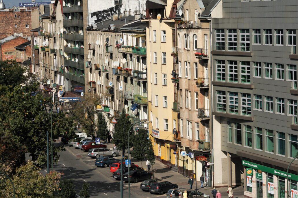 Warszawa. Ulica Targowa około 2011 r. Na zdjęciu z lewej widać kamienicę przy Targowej ujętą po bokach nowymi budynkami. Budynek ma ponownie balkony w bocznych osiach, jednak elewacja całkowicie pozbawiona jest detalu i otynkowana na gładko. Z prawej biurowiec Centrum Milenium wzniesiony w latach 1998–2000 przed firmę Platan Group. Budynek o elewacji z metalicznych paneli był pierwszym biurowcem ówczesnej klasy A, wzniesionym na Starej Pradze. Warto dodać, że jedno ze skrzydeł budynku schowało się za tandetnie odtworzoną makietą fasady kamienicy przy ulicy Brzeskiej. To w trakcie budowy tego wieżowca zawaliła się jedna z oficyn kamienicy przy Targowej 32. Fot. Jerzy S. Majewski