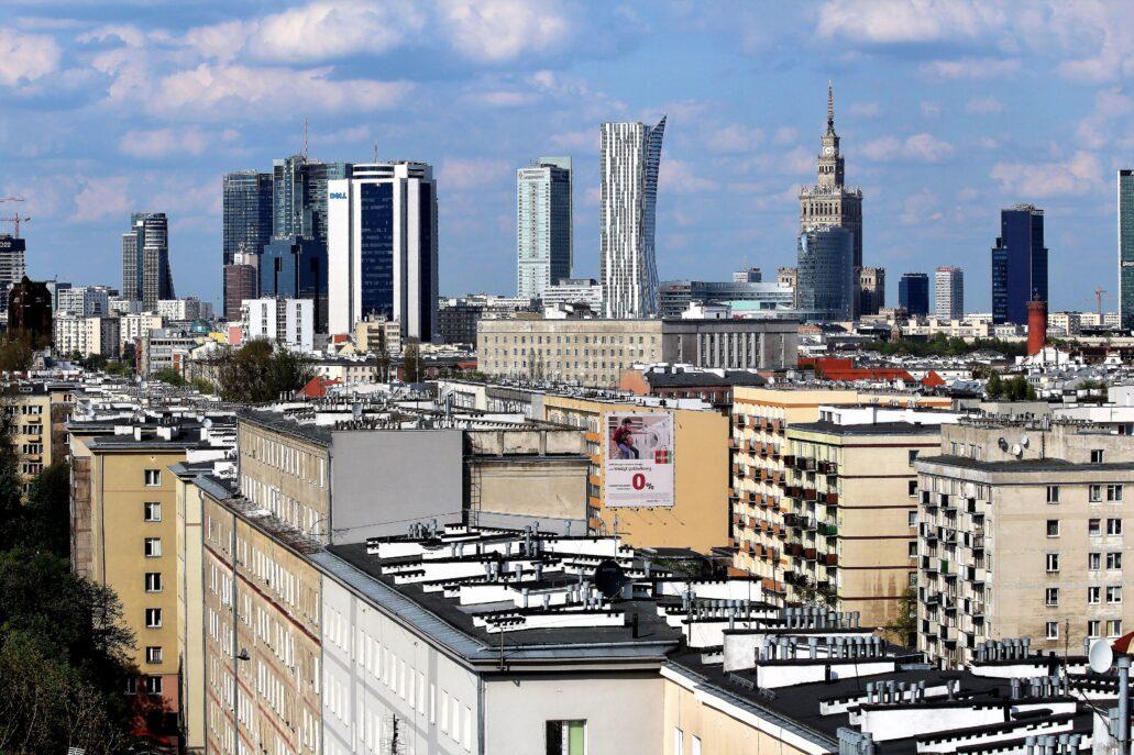"""Warszawa. Widok w kierunku ścisłego centrum miasta z Pałacem Kultury i Nauki w 2015 r. Pałac wciąż dominuje, choć tuż obok wyrosła mu konkurencja wieżowców, mających dachy wyżej od dachu pałacu. Na pierwszym planie zabudowa ulicy Grójeckiej. Budujący się budynek z lewej, to wieżowiec """"Q22"""" o całkowitej wysokości 195 metrów, a wznoszony w miejscu zburzonego hotelu Mercure (Grzybowska róg Jana Pawła II). Najwyższy w panoramie, poza Pałacem Kultury, wydaje się apartamentowiec """"Złota 44"""". Jego dach jest jednak wyżej od dachu PKiN. Fot. Jerzy S. Majewski"""