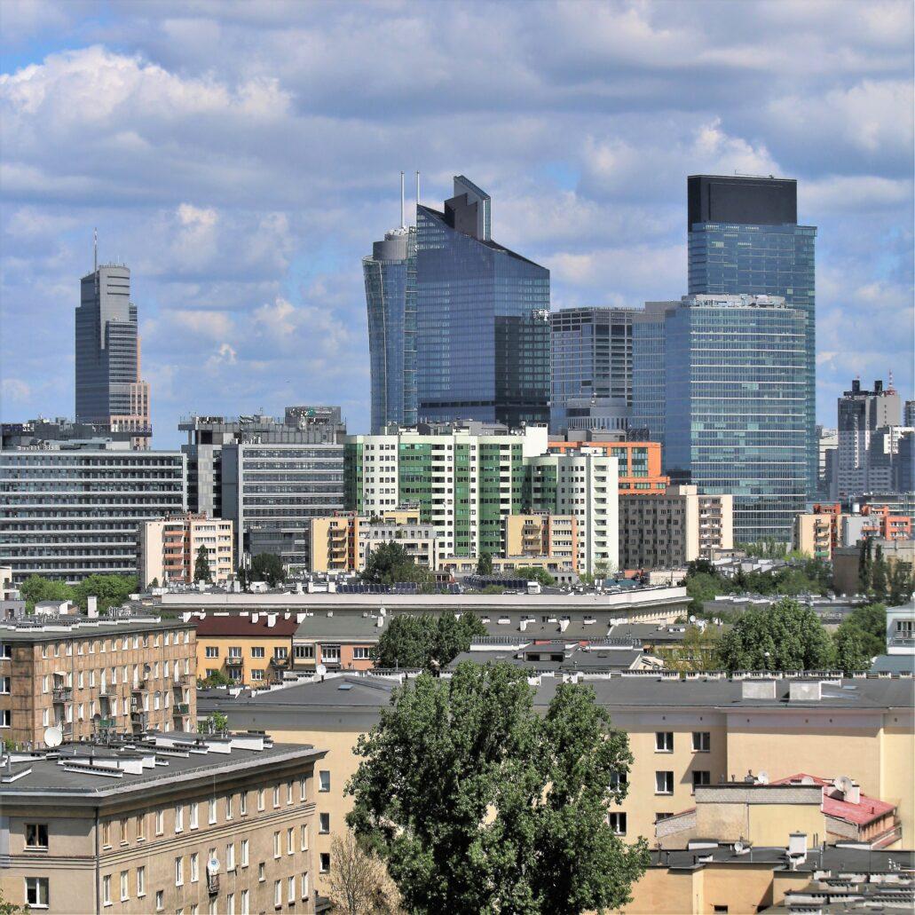 """Zgrupowanie wieżowców pomiędzy Chłodną a Rondem Daszyńskiego. Z lewej przy Chłodnej wieżowiec Warsaw Trade Tower (wysokość całkowita 208 m). W chwili powstania w roku 1999 był to najwyższy wieżowiec w Polsce liczony do dachu (184 m). Drugi po PKiN pod względem wysokości całkowitej. Z prawej widok zamyka zgrabna wieża """"Warsaw Unit"""" firmy Ghelamco o wysokości całkowitej 202 m. Na bliższym planie zabudowa wzdłuż al. Jerozolimskich na Ochocie. Fot. Jerzy S. Majewski"""