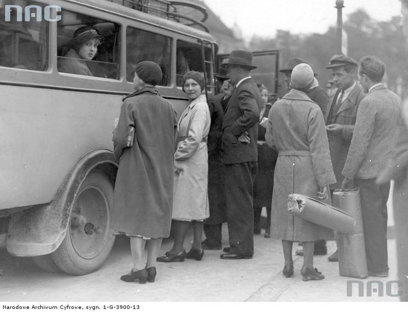 Kraków. Plac św. Ducha. Dworzec autobusu. Pasażerowie wsiadający do autobusu. W tym autobusie szyby były opuszczane. Na dachu widać złożone rowery. 1932 r. Fot. Narodowe Archiwum Cyfrowe