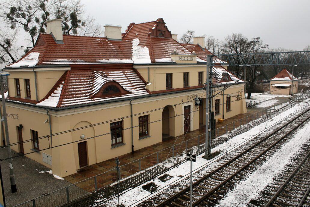 Modlin. Na zakończenie fotografia dworca w Modlinie, usytuowanego również pod Warszawą, ale na linii biegnącej na północ. Dworzec w Modlinie miał duże znacznie ideowe. Znajdował się bowiem w sąsiedztwie zajmowanej teraz przez Wojsko Polskie twierdzy modlińskiej. Budynek został odremontowany w związku z modernizacją linii do Gdańska, a wielkie chwile przeżywał od chwili otwarcia lotniska w Modlinie w 2912 r. do początku lockdownu w 2020 r. i zawieszenia działalności lotniska. Na dworcu pasażerowie samolotów przesiadają się z pociągu do autobusów dowożących ich na lotnisko. Fot. Jerzy S. Majewski