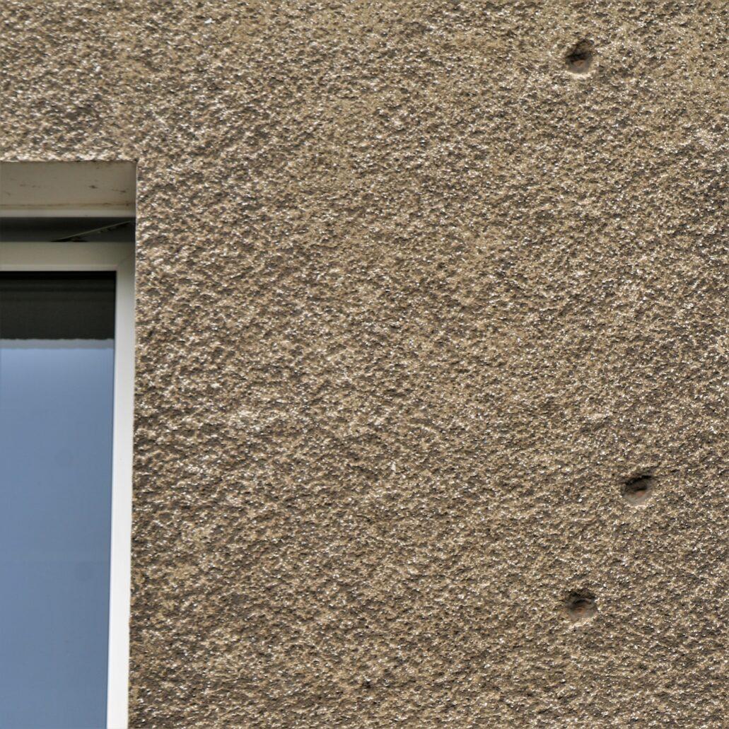 Warszawa. Narbutta 8. Wydaje się, że tynki w starszej części są lepszej jakości, niż te w nowszej części budynku. Na zdjęciu fragment ściany starszej części z widocznymi na niej śladami po odłamkach z 1939 lub 1944 r. Fot. Jerzy S. Majewski